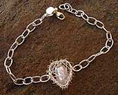 Silver bracelet with a caged pink heart