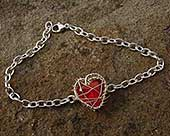 Silver bracelet with a caged red heart