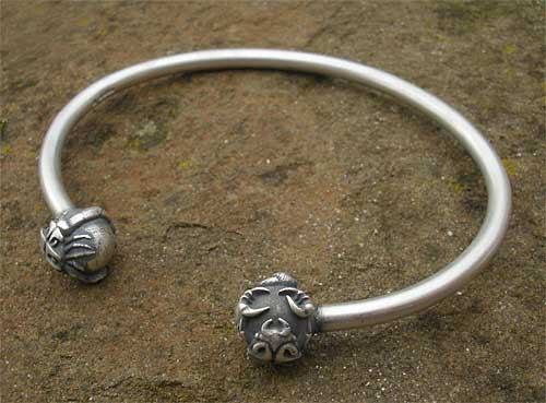 Silver torc charm bracelet in a matt finish with scorpion heads