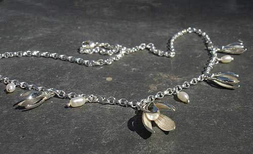 A necklace consisting of a silver chain fashioned with snowdrops