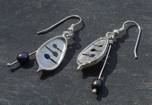 Celtic earrings with enamel detail and peacock pearls threaded onto a silver wire